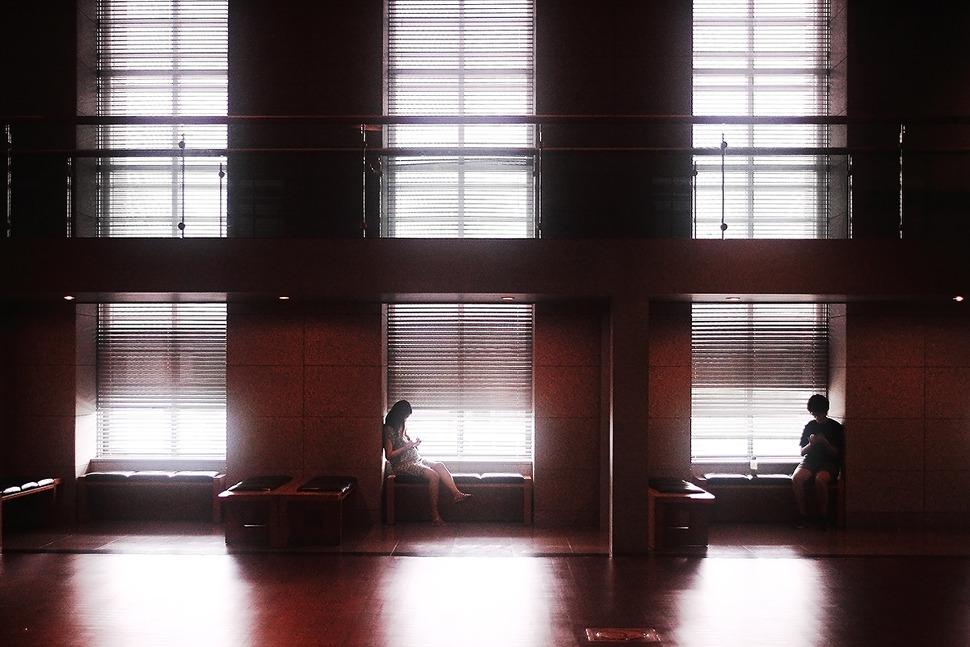 어두운곳에 틈새로 삐져나오는 빛이인상적이라 찍은사진으로 한가로이 핸드폰을 만지는 임산부와 남자아이가 담겨있다.
