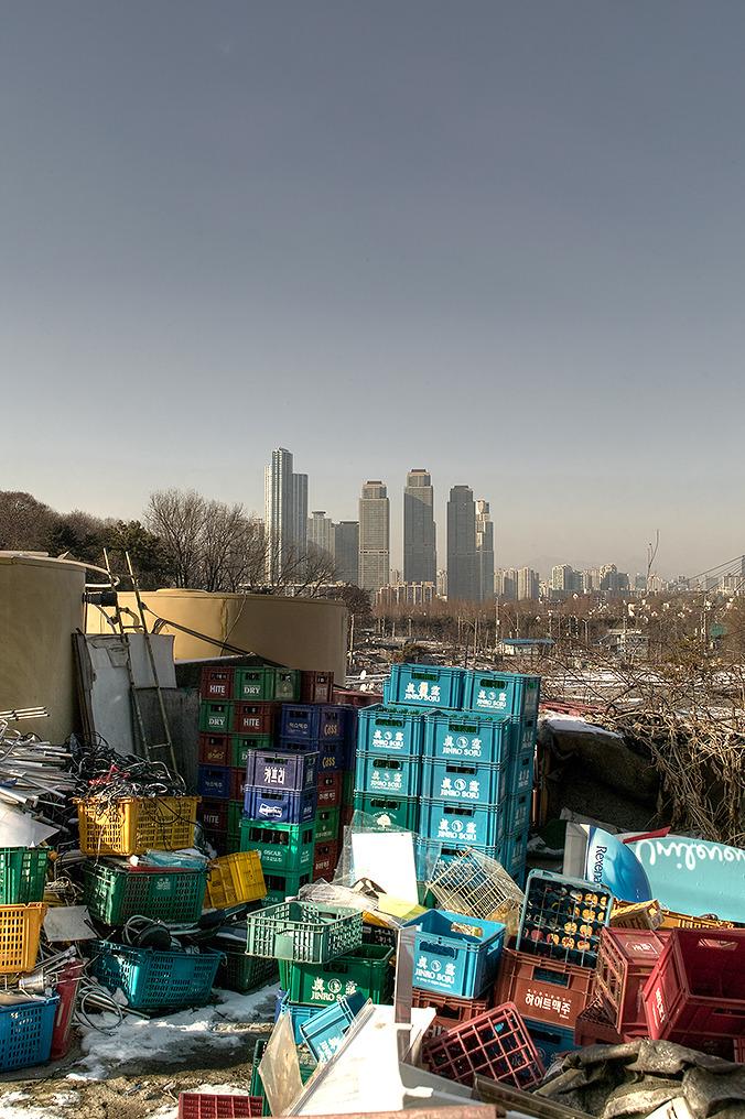 타워펠리스가 보이는 구룡마을에서 촬영한 사진-앞으로는 쓰레기와 재활용품들이 보이고 배경에는 타워펠리스의 모습이 보인다.